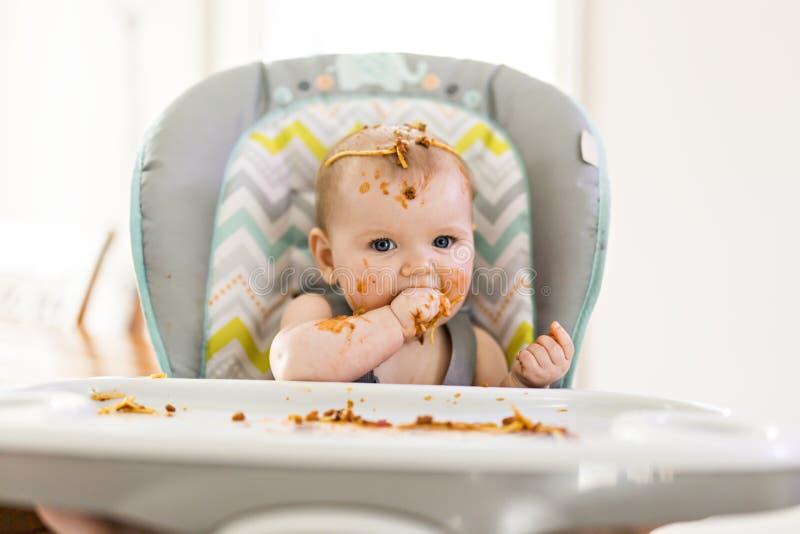 Pequeño bebé que come su cena y que hace un lío imágenes de archivo libres de regalías
