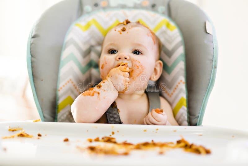 Pequeño bebé que come su cena y que hace un lío imagen de archivo libre de regalías