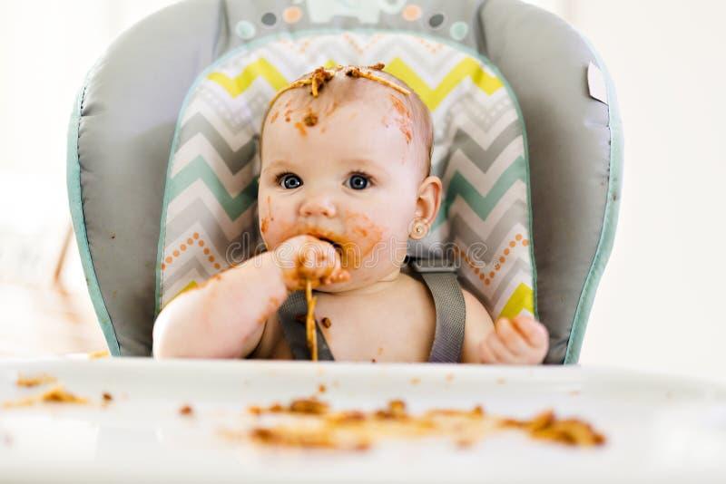 Pequeño bebé que come su cena y que hace un lío foto de archivo