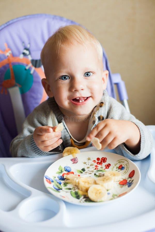 Pequeño bebé que come un plátano lindo imagen de archivo