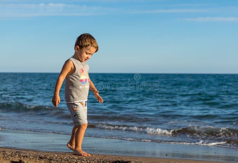 Pequeño bebé que corre a lo largo de la costa del mar Emociones humanas positivas, sensaciones, fotografía de archivo libre de regalías