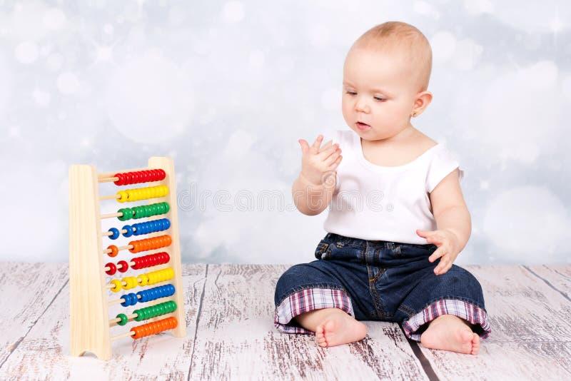 Pequeño bebé que cuenta con el ábaco imagenes de archivo