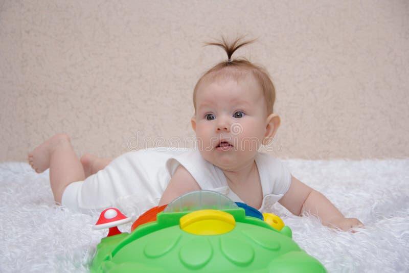 Pequeño bebé que juega con un juguete imagen de archivo