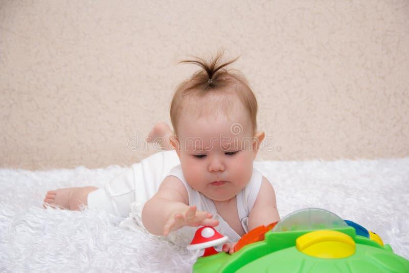 Pequeño bebé que juega con un juguete foto de archivo