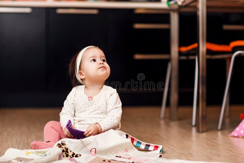 Pequeño bebé que juega en el piso de la cocina fotos de archivo libres de regalías