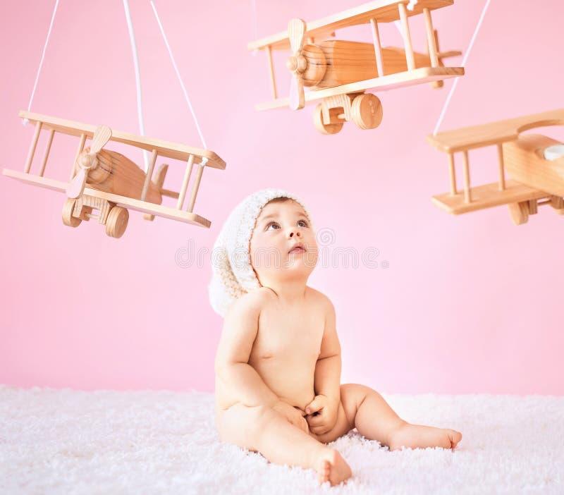 Pequeño bebé que juega los aviones de madera del juguete fotografía de archivo libre de regalías