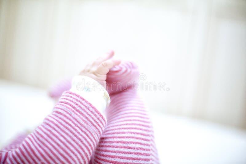 Pequeño bebé que miente en cama y que lleva a cabo sus piernas imagen de archivo