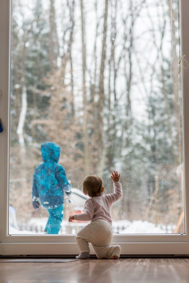 Pequeño bebé que mira a un hermano el jugar en nieve imagenes de archivo
