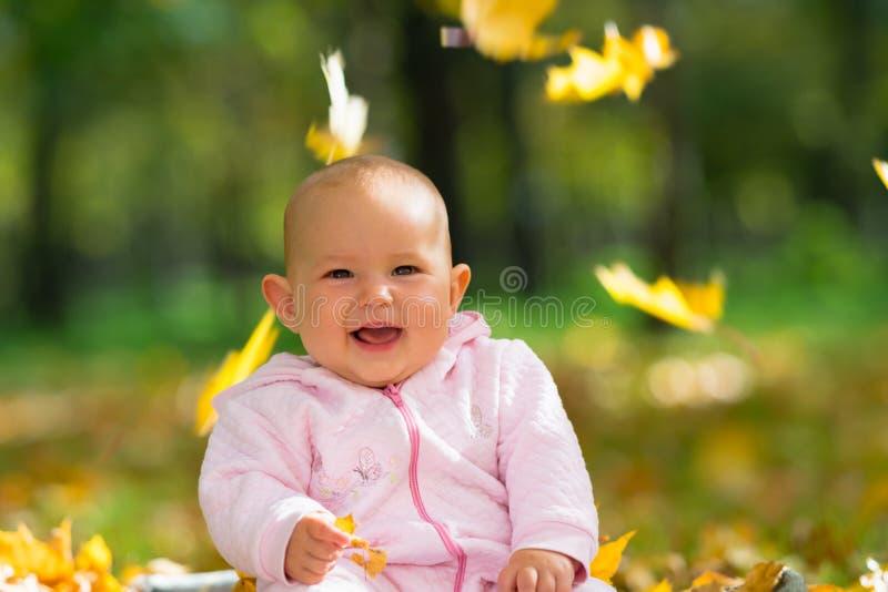 Pequeño bebé que ríe como ella juega con las hojas imagen de archivo libre de regalías
