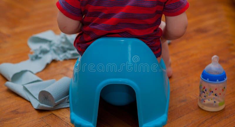 Pequeño bebé que se sienta en el pote de cámara con el papel higiénico y el pacificador en un fondo marrón fotografía de archivo libre de regalías