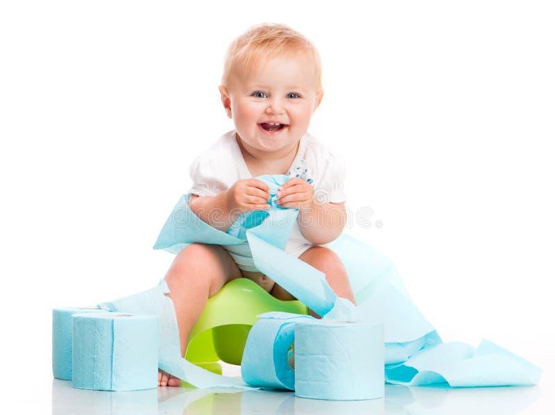 Pequeño bebé que se sienta en un pote imagen de archivo