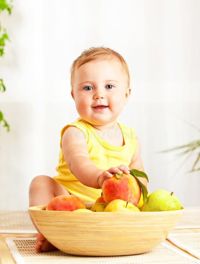 Pequeño bebé que sostiene las frutas frescas imagenes de archivo