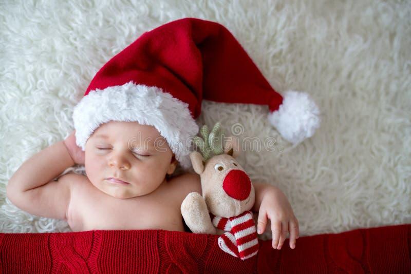 Pequeño bebé recién nacido durmiente, sombrero de Papá Noel que lleva foto de archivo