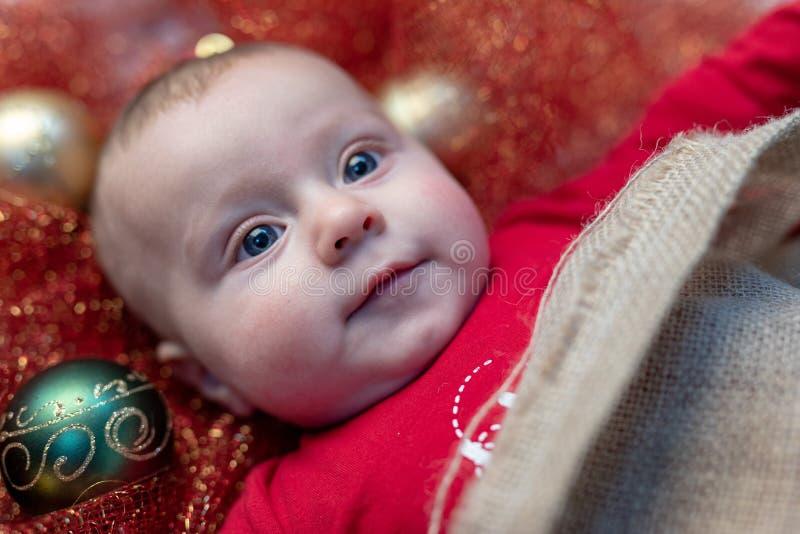 Pequeño bebé recién nacido lindo con las chucherías de la Navidad fotos de archivo