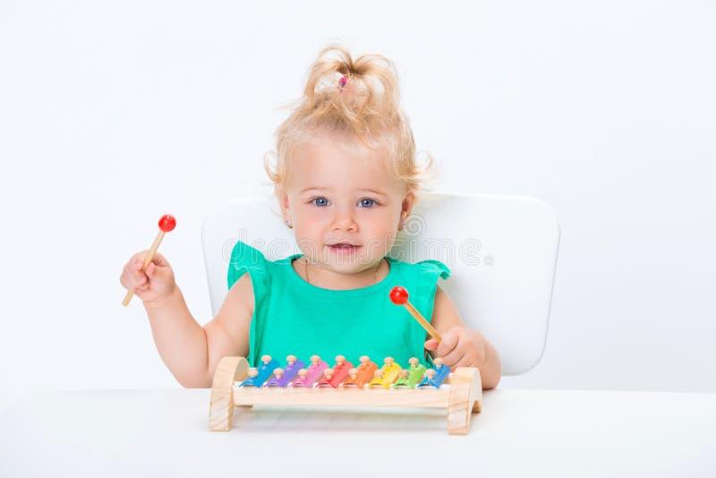 Pequeño bebé rubio sonriente lindo del niño que juega con el xilófono musical del juguete aislado en el fondo blanco foto de archivo libre de regalías