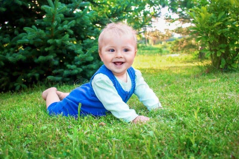 Pequeño bebé sonriente lindo que miente en una hierba verde fresca en un parque foto de archivo libre de regalías