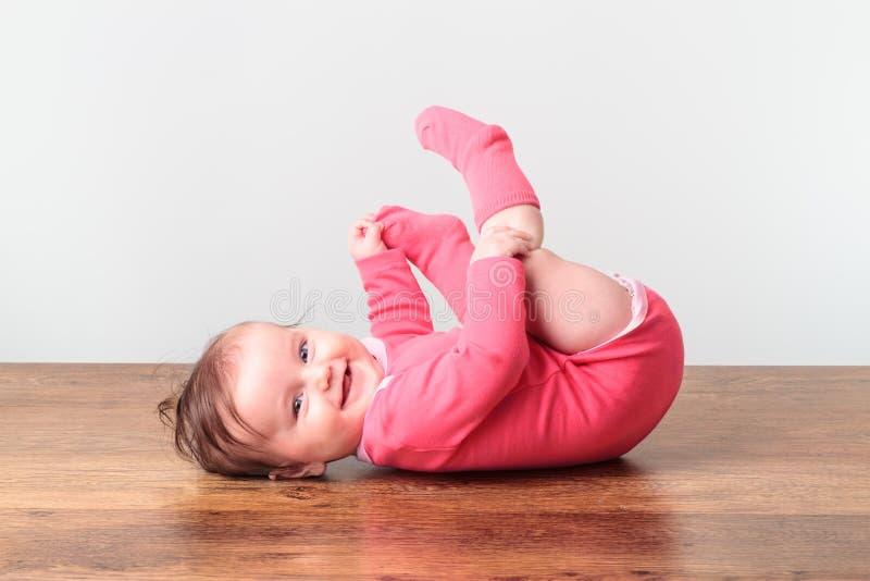 Pequeño bebé sonriente que juega con sus pies foto de archivo libre de regalías