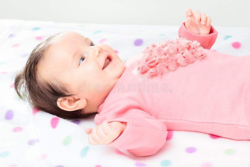 Pequeño bebé sonriente que miente en la manta de los lunares imágenes de archivo libres de regalías