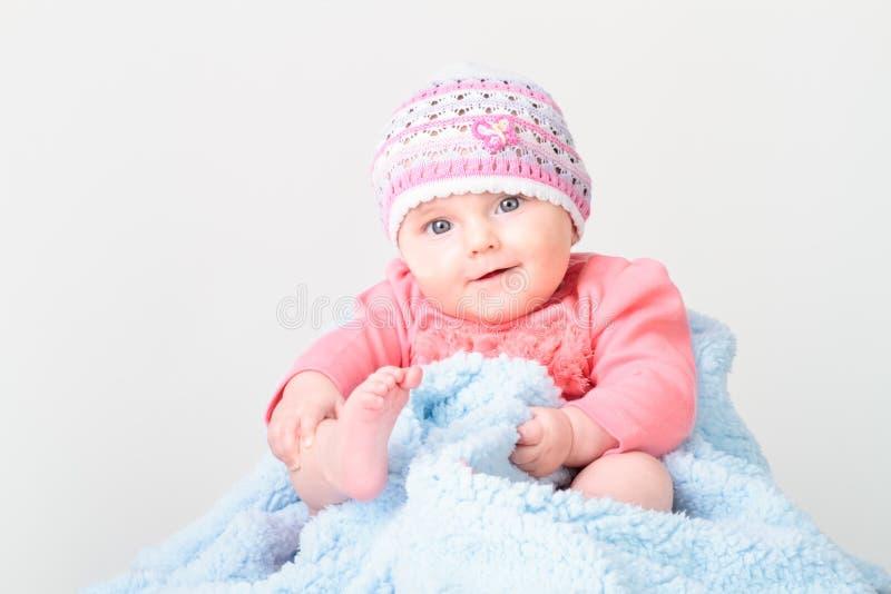 Pequeño bebé sonriente que se sienta en la manta imagen de archivo