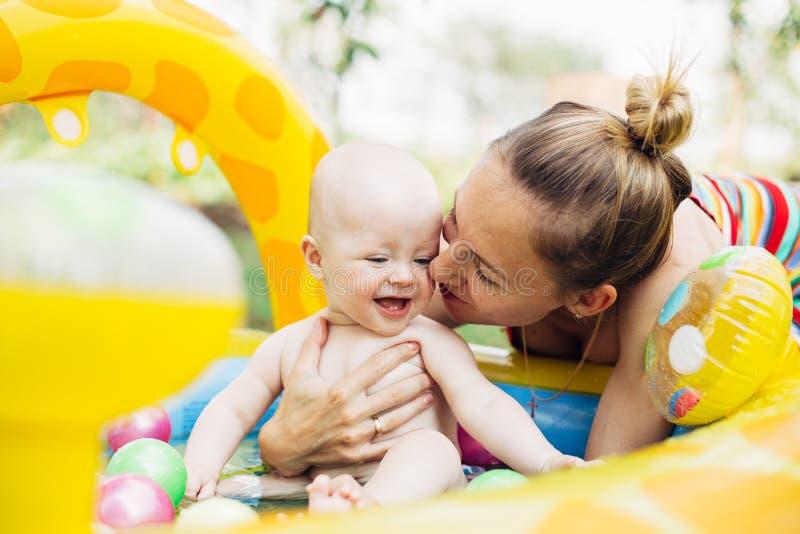 Pequeño bebé y su madre que juegan en la piscina Verano Sonrisa imagenes de archivo