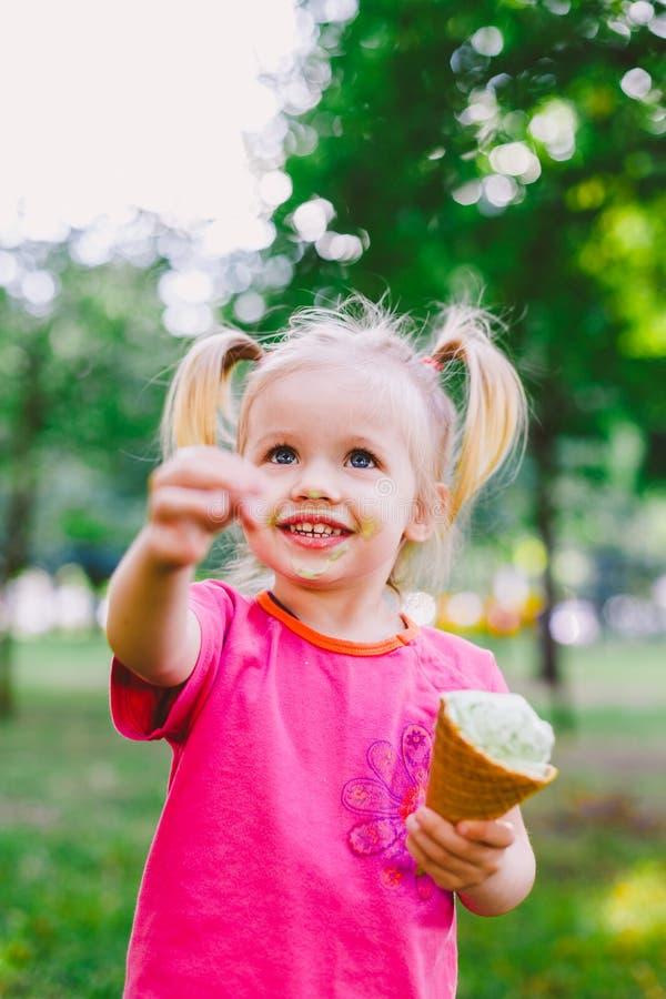 Pequeño blonde divertido de la muchacha que come el helado azul dulce en una taza de la galleta en un fondo verde del verano en e foto de archivo