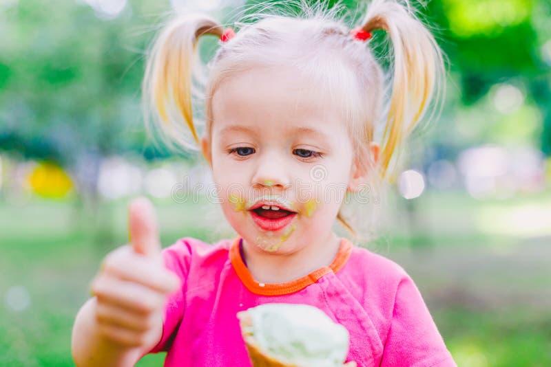 Pequeño blonde divertido de la muchacha que come el helado azul dulce en una taza de la galleta en un fondo verde del verano en e fotografía de archivo