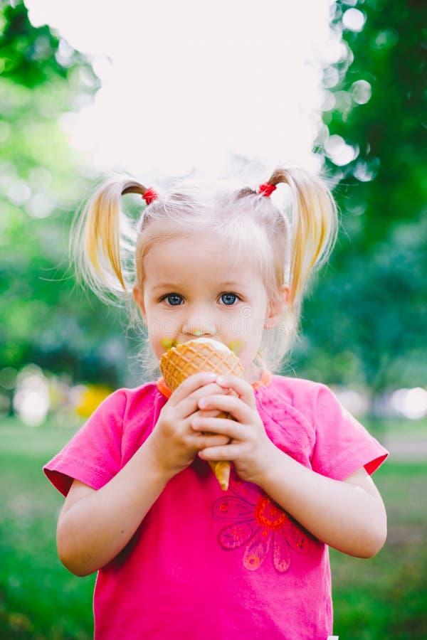 Pequeño blonde divertido de la muchacha que come el helado azul dulce en una taza de la galleta en un fondo verde del verano en e foto de archivo libre de regalías