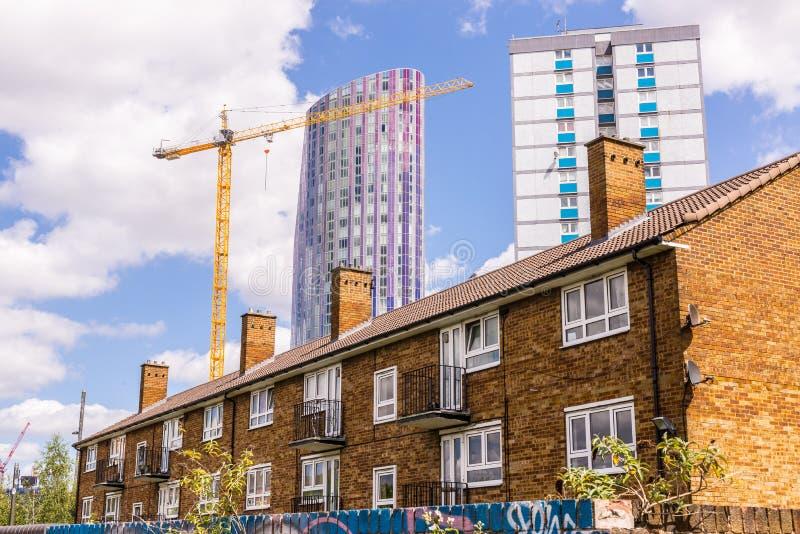 Pequeño bloque de viviendas con la casa del consejo y el rascacielos moderno imagenes de archivo