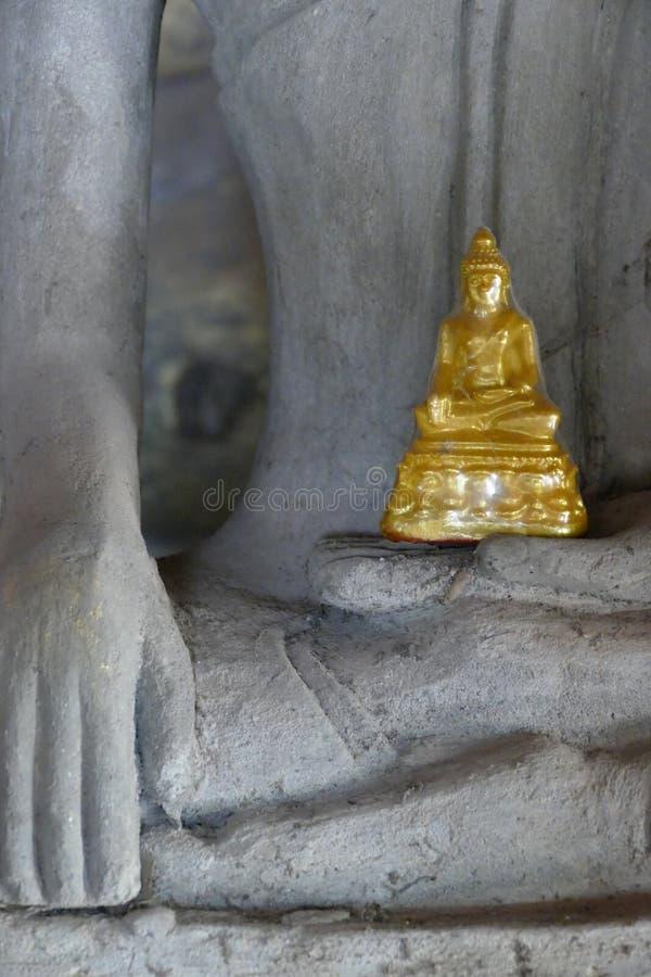 Pequeño Buda de oro que se sienta en las manos de Buda grande foto de archivo libre de regalías