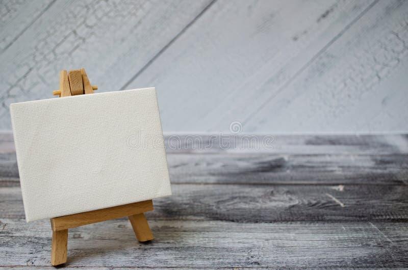 Pequeño caballete con una lona en blanco sobre blanco Viejo fondo de madera y espacio grande de la copia para su muestra y texto imagenes de archivo
