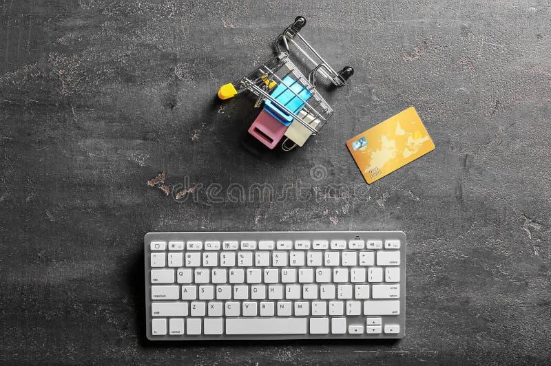 Pequeño carro con el teclado de ordenador y tarjeta de crédito en fondo gris Compras en l?nea imágenes de archivo libres de regalías
