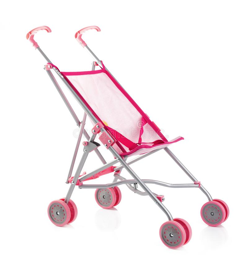 Pequeño carro de bebé o cochecito rosado de la muñeca aislado en blanco fotos de archivo