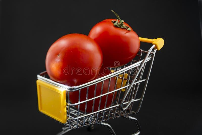Pequeño carro de la compra con los tomates en un fondo blanco imagen de archivo