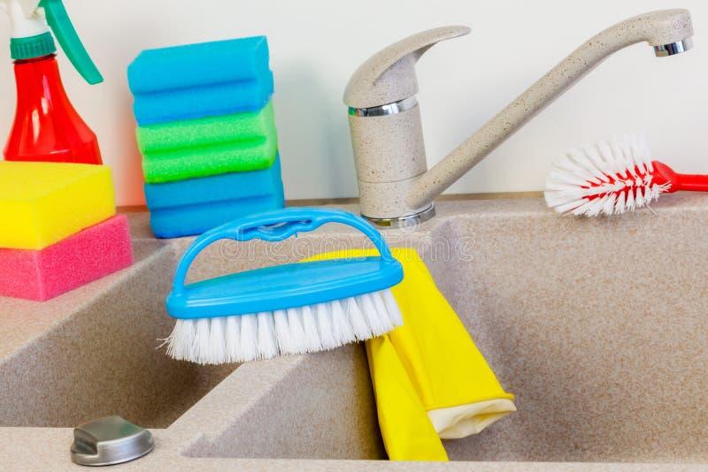 Pequeño cepillo y esponjas en fregadero de cocina cerca del golpecito fotografía de archivo
