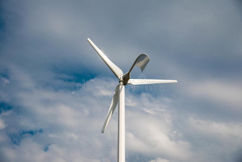 Pequeño cierre eolian blanco de la turbina de viento para arriba, cielo azul con las nubes blancas imágenes de archivo libres de regalías