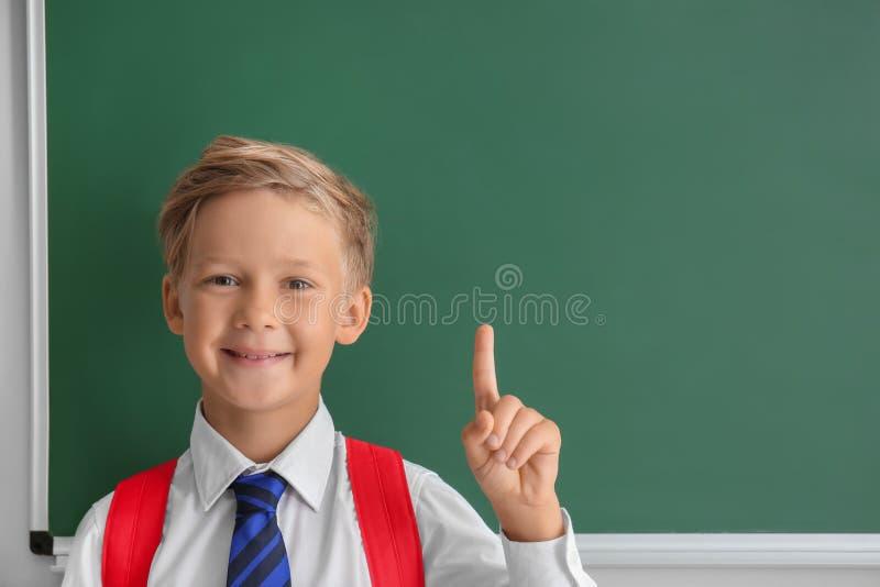 Pequeño colegial lindo con el dedo índice aumentado cerca de la pizarra en sala de clase fotografía de archivo