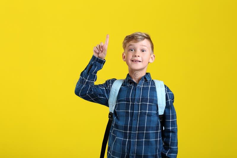 Pequeño colegial lindo con la mochila y el dedo índice aumentado en fondo del color fotos de archivo libres de regalías
