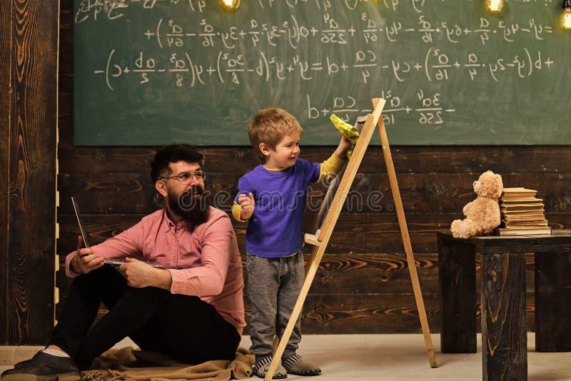 Pequeño colegial que limpia la pizarra Profesor sonriente en los vidrios que se sientan en el piso mientras que el niño se está d imagenes de archivo