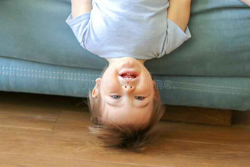 Pequeño colgante divertido lindo del bebé al revés en el sofá que mira la cámara, sonriendo foto de archivo libre de regalías