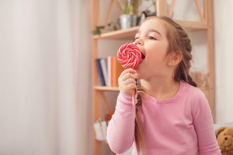 Pequeño concepto lindo de la celebración de la muchacha en casa que come la piruleta fotos de archivo libres de regalías