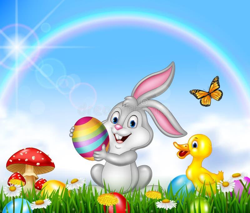Pequeño conejito feliz que sostiene un huevo de Pascua con el fondo de la naturaleza libre illustration