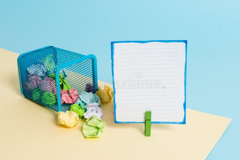 Pequeño cubo de la basura inclinado por completo de papel coloreado arrugado y de una pinza que cuelga una nota de papel colorida foto de archivo