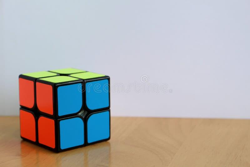 Pequeño cubo del bolsillo 2x2 de Rubik en una tabla foto de archivo libre de regalías