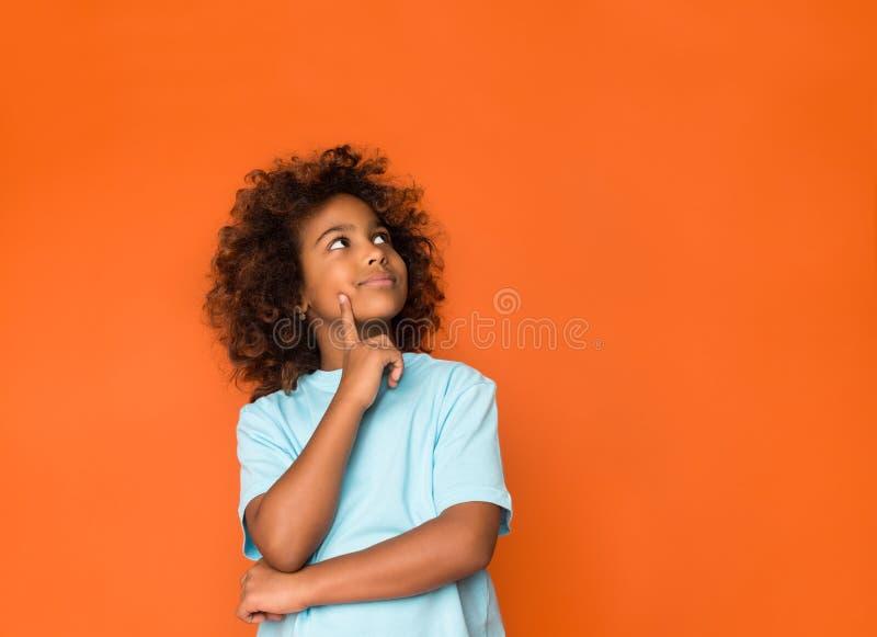 Pequeño daydreamer Finger de la tenencia de la muchacha en la barbilla y la mirada lejos imagenes de archivo
