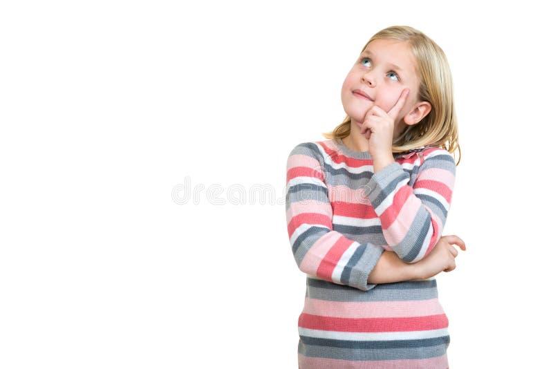 Pequeño daydreamer Niña alegre que sostiene el finger en la barbilla y que mira lejos foto de archivo libre de regalías