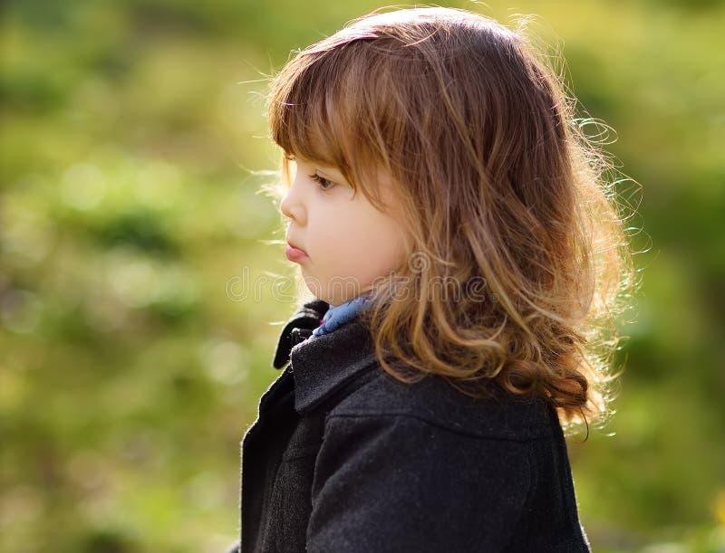 Pequeño de la muchacha retrato infeliz lindo al aire libre en día soleado de la primavera imagen de archivo libre de regalías