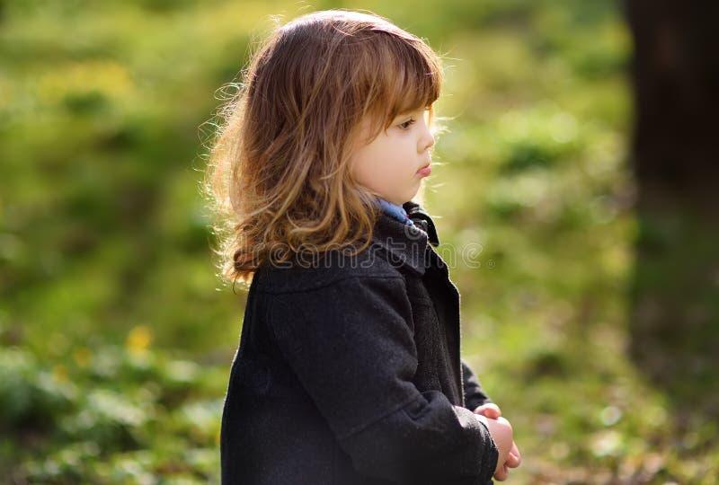 Pequeño de la muchacha retrato infeliz lindo al aire libre en día soleado de la primavera fotos de archivo libres de regalías