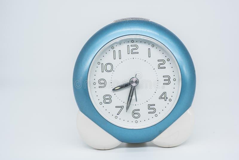 Pequeño despertador con la frontera azul sobre el fondo blanco foto de archivo libre de regalías