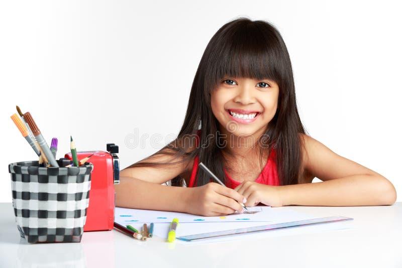 Pequeño dibujo asiático feliz lindo de la muchacha con los lápices imagenes de archivo