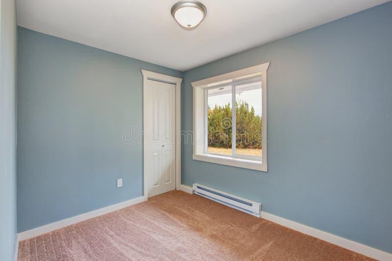 Pequeño dormitorio azul claro en casa vacía foto de archivo